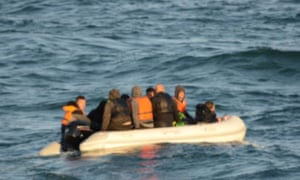 Migrants and rescuers on boat at sea