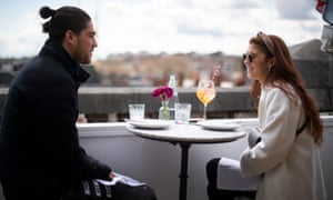 A couple sit in a restaurant on the roof of the Selfridges department store on Oxford Street, London.