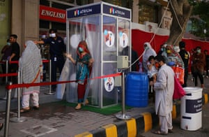 People are disinfected before entering a mall after the government eased coronavirus restrictive measures in Karachi.