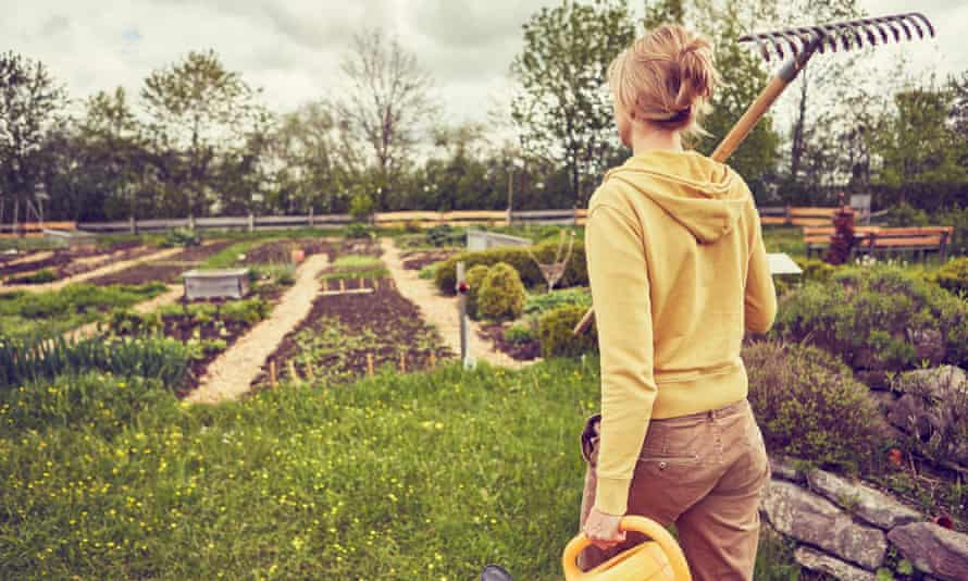 A woman carrying a rake and watering can in a garden