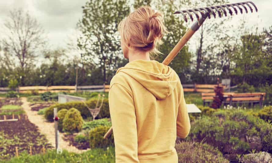 A woman carrying a rake