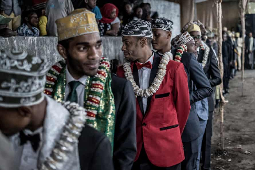 Men wearing ceremonial scarves and garlands of flowers perform a traditional dance