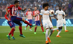 Angel Correa of Atletico Madrid shoots at goal as Luiz Gustavo of Marseille tries to block.