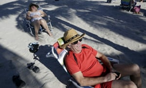 Tourist Robert Tembley, 61, of Montreal, Canada, right, relaxes on the beach in Hollywood, Florida. Visits by Canadians are expected to be down by 8% this year due to the weak Canadian dollar.