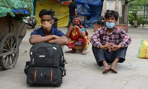 Stranded people who have their train tickets sit outside the railway station in New Delhi.