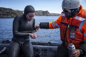 Ercümen warms her hands with tepid water after her first dive