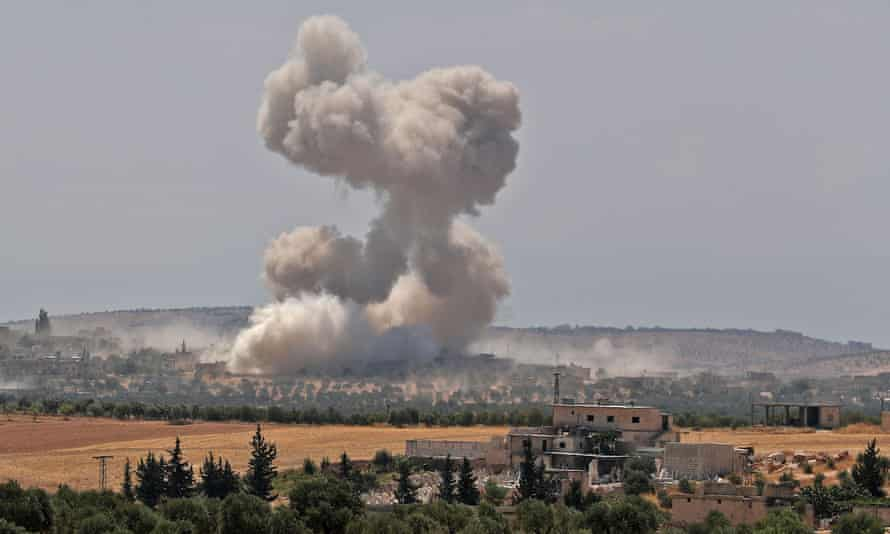 Smoke billows above buildings during a reported airstrike by pro-regime forces in Syria's Idlib province.