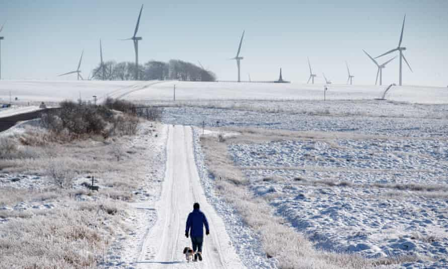 Person and dog enjoying a snowy walk through Whitelee Windfarm in North Ayrshire