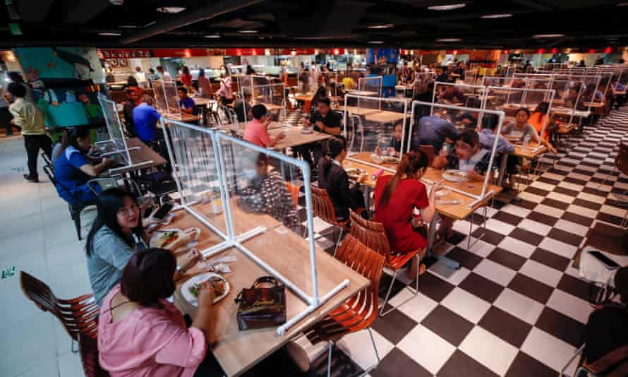 People eat lunch separated plastic screens, implemented to reduce the spread of Covid-19, at a food court in Bangkok