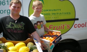 Two young men hold crates of fruit in front of a branded van