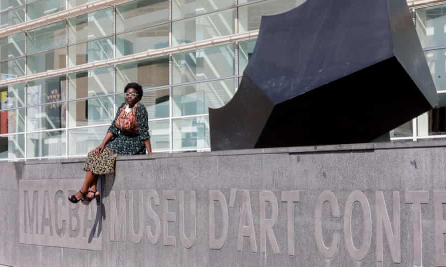 Elvira Dyangani Ose sitting on a wall bearing the museum's logo and name in relief along its length, with a dark, jagged abstract culture to her left on top of the wall