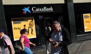 A man puts money in his wallet outside a CaixaBank branch in Barcelona, Spain