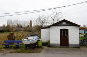 A boat sits outside the old custom post on the river at the Belgium-France border in Leers-Nord