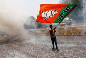 New Delhi, India. A BJP supporter waves a party flag as he celebrates the initial election results