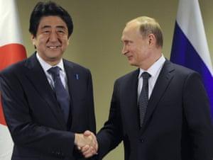 Shinzo Abe and Vladimir Putin shake hands.