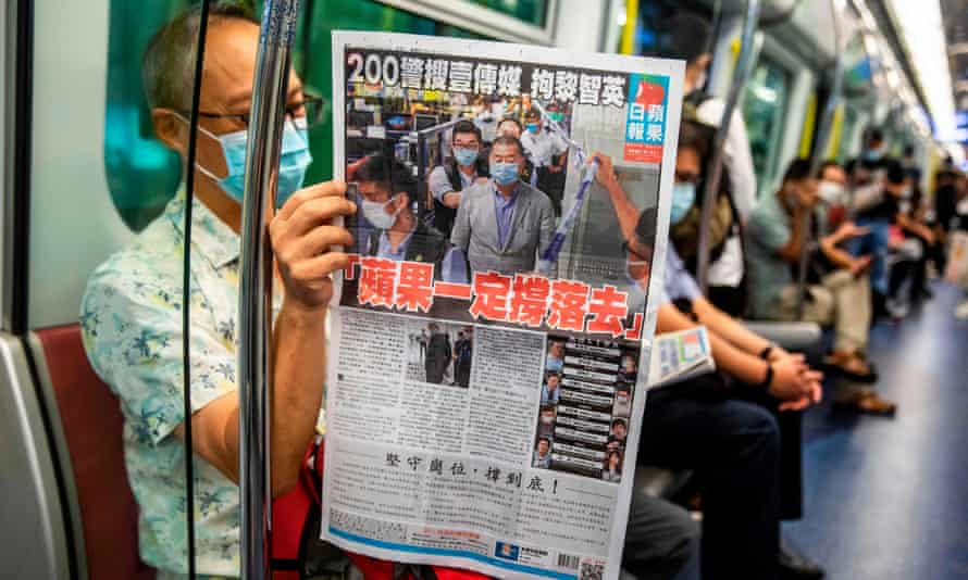 A commuter reads a copy of the Apple Daily newspaper.