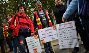 A demonstrator holds a sign reading 'Civil servants = scapegoats' during a protest in Nantes against the changes.