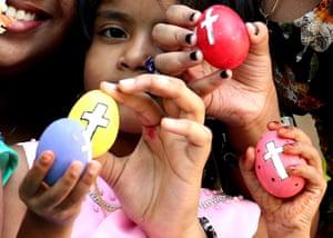 Girls hold coloured Easter eggs