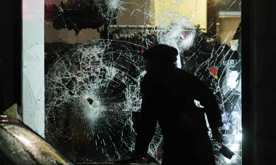 A person prepares to clean up broken glass outside a shop in Leipzig.