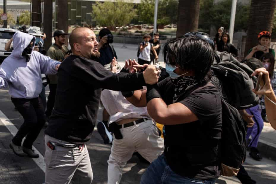 Anti-vaccine demonstrators and counter protesters clash during a protest in front of city hall in Los Angeles on 14 August.