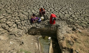 Women fetch water from a makeshift well at a dried-up lake in Chennai.