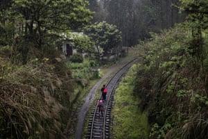 Villagers walk on the railway tracks near Bagou