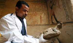 An archeologist holds an ancient mummified bird, found inside the newly discovered tomb of Tutu burial site in Sohag, Egypt.