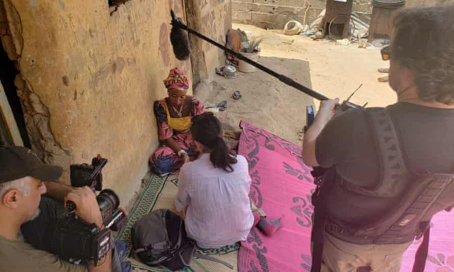 Mellissa Fung sitting on a mat in a dusty street opposite Gambo, talking, with a cameraman and microphone man in the foreground