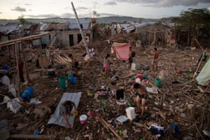 Residents bathe, wash and pump water at their destroyed village following the damage caused by Typhoon Vamco.