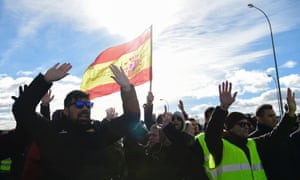 "Taxi drivers hold a Spanish flag reading ""Justice"" in front of policemen."