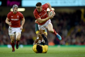 Josh Adams of Wales goes through the challenge of Will Genia of Australia.