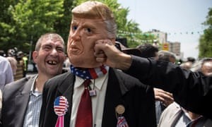 Demonstrators punch a man in a Donald Trump mask during an anti-US rally in Iran.