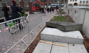 People pass by the memorial stone marking the site of Strasbourg's Old Synagogue after it was vandalised in March.