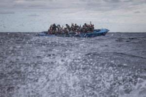 Moroccans and Bangladeshis wait on an overcrowded wooden boat, as aid workers from the Spanish Open Arms ship approach them off the Libyan coast.
