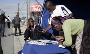 An employee of a bank checks an identity document via mobile phone as he sells accounts on the street in Khayelitsha, a township outside Cape Town, South Africa
