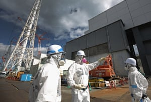 Workers stand outside reactor 4 as they continue the radiation decontamination process at the embattled Fukushima Daiichi nuclear power plant.