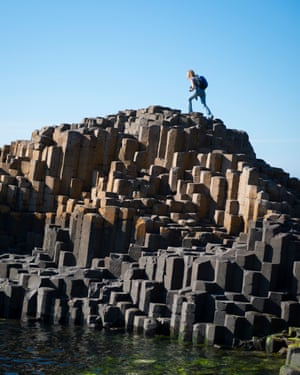 A woman visiting Northern Ireland climbs to the top of a rock outcropping at Giant's Causeway in Northern Ireland.