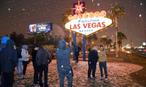 People take photos in front of the Welcome to Fabulous Las Vegas sign as snow falls.