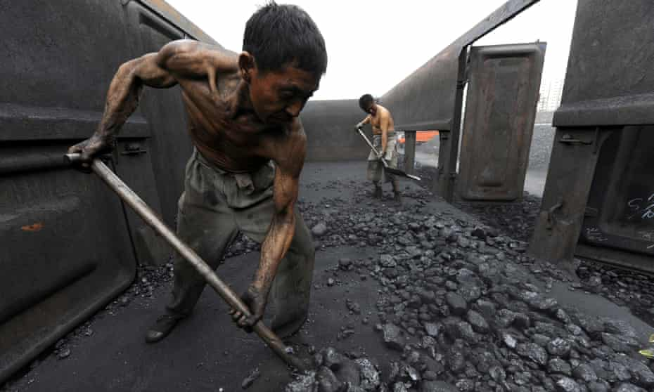 Workers shovel coal at a storage depot in Hefei, China