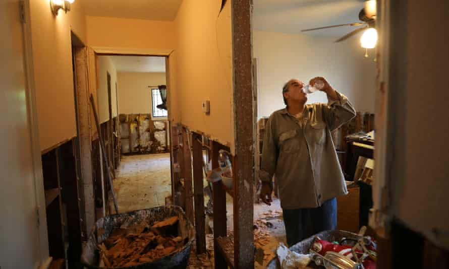 Rogelio Salina takes as break as he helps a neighbor to clean a house in East Houston damaged by Harvey.