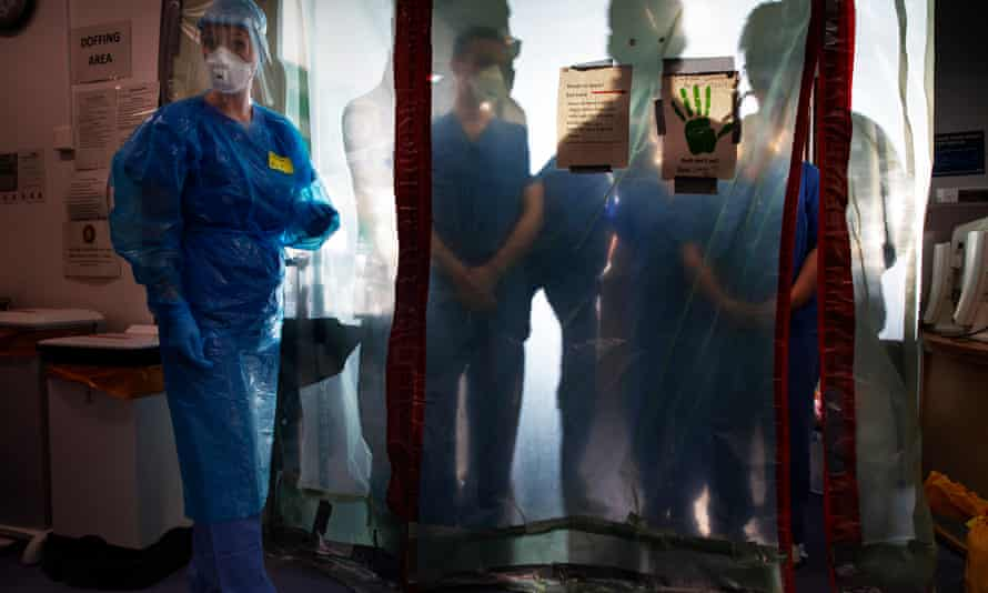 Nurses in a Covid-19 ward check their personal protective clothing.