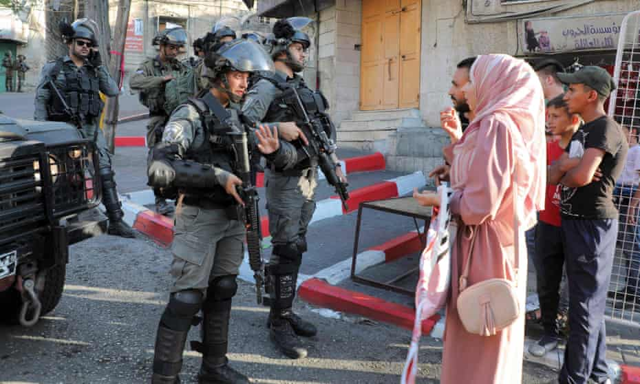Israeli border guards block a street to Palestinians in the city of Hebron in the Israeli-occupied West Bank, 18 June 2021.
