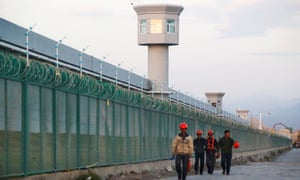 Workers walk by the perimeter fence of re-education camps in Xinjiang. UN sources say the body's counter-terrorism czar will visit the province this week.