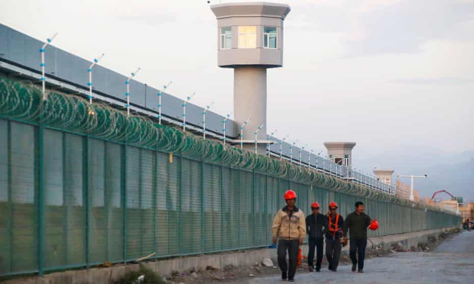 Workers walk by the perimeter fence of an 'education centre' in Xinjiang.