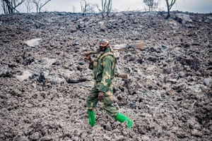 A Congolese soldier walks on cooled lava as he provides security for people evacuating from Goma in the aftermath of the eruption of the Nyiragongo volcano.