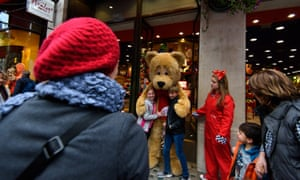 Tourists hug Hamleys bear outside store in London