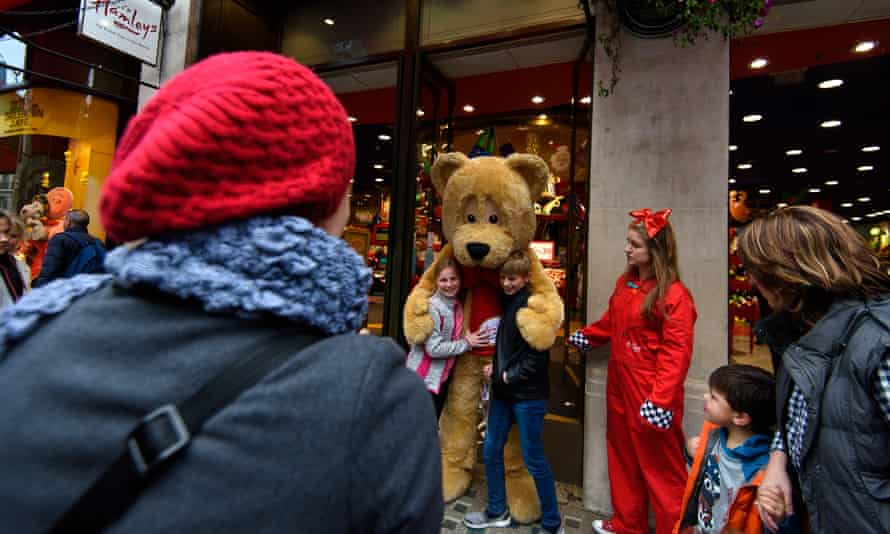 Tourists hug Hamleys bear outside store in London