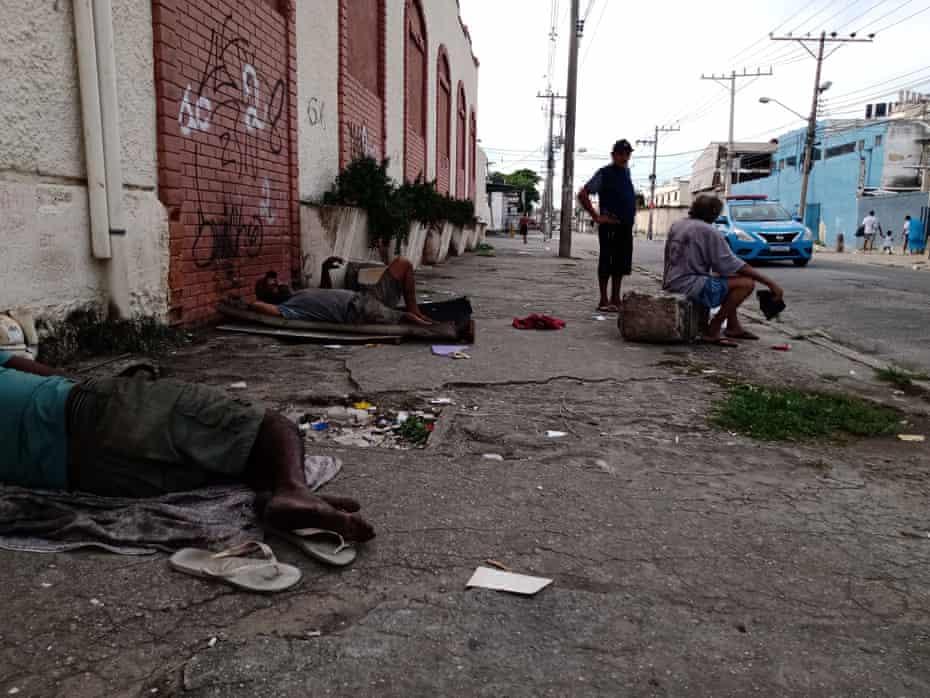 Homeless men lay on the sidewalk of the rubbish strewn skid row that is Rio de Janeiro's Regeneration Street.