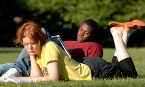 Students lying on grass reading books in a park