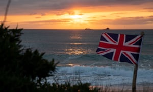 The sun sets behind a Union Jack flag on Constantine Bay beach, Cornwall, on the evening British Prime Minister Boris Johnson announced a 'road map' to begin the end of lockdown due after Covid-19.
